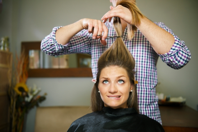 Nervous brunette woman getting haircut at a salon