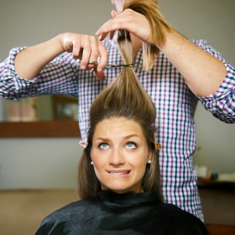 female client in hairdresser shop uncertain about cutting hair and biting lips